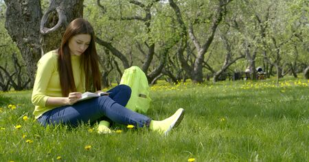 Young beautiful girl with long dark hair sitting in nature on a green field with dandelions under a tree, reading a book. Next to it is a yellow backpack.