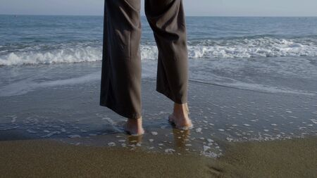 Legs in wide trousers stand barefoot on the sandy beach by the sea, they are washed by waves.