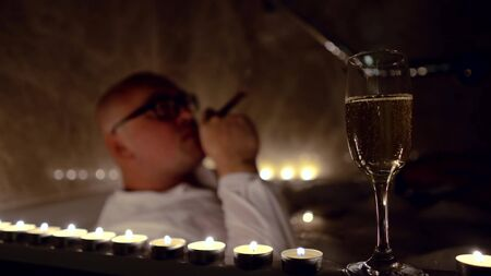 Bald drunk man lying in the bathroom in clothes by candlelight and Smoking a cigar. foreground glass with alcohol champagne Фото со стока
