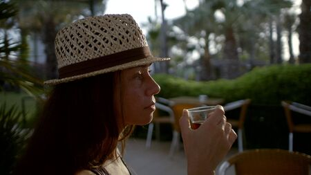 Close-up portrait of a dark-haired woman in a hat, she is middle-aged, who drinks a drink from a glass glass, she smiles and holds a phone in her hand. Side view.