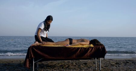 female master is massaging naked body of woman client lying on table on sea coast Imagens