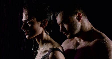 Portrait of a passionate beautiful couple with bare shoulders, which are under heavy rain on a black background. A man kisses a woman on the neck while behind her.
