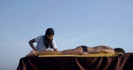 female masseuse is massaging body of client lying on table outdoors, tilt up Imagens