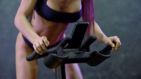 the athletic body of a girl with long purple hair, in a topic and in panties, which is engaged on a stationary bike.