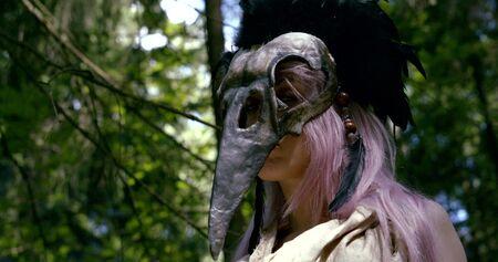 long purple haired girl takes off strange skull mask Zdjęcie Seryjne
