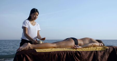 thai woman is performing oil massage for client on sea shore outdoors Imagens