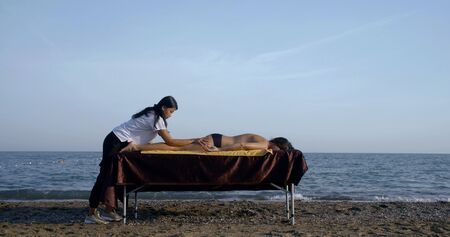 massage therapist works on sandy beach against endless ocean Imagens