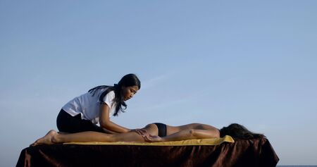 Close-up massage on the seashore on a special table. Asian masseuse massages her legs completely, ass, back of a dark-haired tanned girl against the blue sky and the sea. Imagens