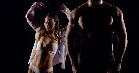 Pareja joven bailando bajo la lluvia sobre un fondo oscuro. Chica morena mojada en camisa blanca y ropa interior blanca y silueta de hombre alto musculoso con torso. Foto de archivo