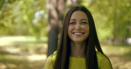 exciting brunette in yellow top smiles standing in park