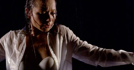 portrait of a dark-Haired girl in a white shirt and a white bra, she stands on a black background in the rain, dancing. Stock fotó