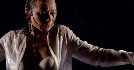 portret van een donkerharig meisje in een wit overhemd en een witte beha, ze staat op een zwarte achtergrond in de regen, dansend. Stockfoto