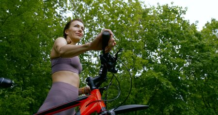 Beautiful slim girl in a t-shirt and the tights carries the bike by the handlebars and come along among the trees and green grass.