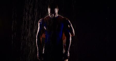 half muscular man is standing under rain in darkness, female hands are stroking his body from back