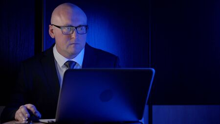 bald businessman, in a jacket with a tie and glasses, middle-aged, sitting in the dark behind a laptop, looking at the computer screen in surprise, staring, nervous, straightens glasses. Фото со стока