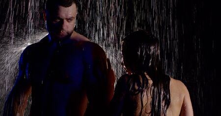 Naked big man standing on a black background in the heavy rain, next to him is a naked girl and runs his hands over his body.