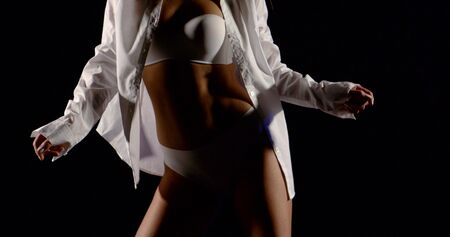 beautiful figure of a girl in white underwear and white shirt. She's dancing on a black background. Imagens
