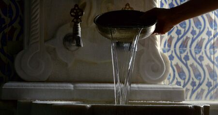 l'homme verse de l'eau d'une tasse en bronze dans un lavabo en pierre dans une pièce sombre, en gros plan