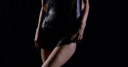The figure of a woman in a black tight dress on a dark background in heavy rain. Her hips and legs close up.