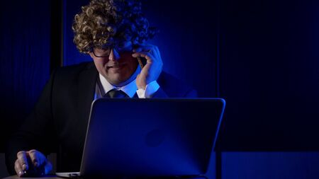 comic adult man dressed in business suit and funny curly wig on head, calling working in office