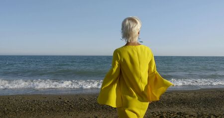 A blonde with short hair goes barefoot on a sandy-pebble beach, wet her feet in the wavy sea, against the blue sky in the wind, on her yellow dress. Rear view. Stock Photo
