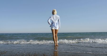 A blonde girl with a short haircut stands on a sandy-pebble beach, wet her feet in the waves of the sea, against the blue sky towards the wind, she is wearing a light shirt and white shorts. Stock Photo
