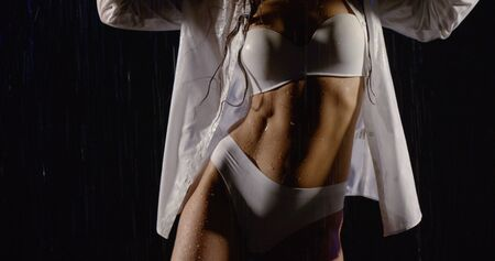 close-up of slender female healthy body in white lingerie and shirt in the rain dancing in the dark Фото со стока