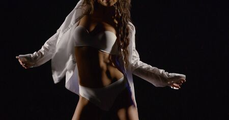 close-up of slender female healthy body in white lingerie and shirt dancing in the dark seductive dance