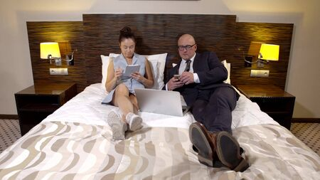 adult spouses are resting in bedroom in evening, woman is viewing tablet, man is using smartphone