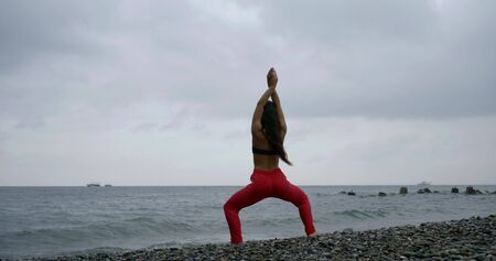 long haired lady in purple pants meditates on rocky beach Stock fotó