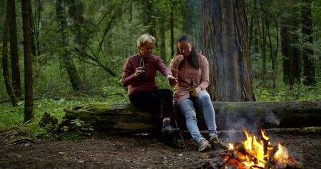 aged woman and daughter sit on fallen tree and laugh Фото со стока