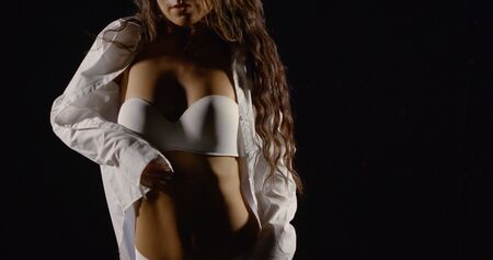excited woman is moving erotically in darkness, touching his body, she is dressed in white male shirt and bra