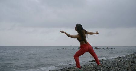 dancer woman is training on sea shore, doing physical exercises with squatting and stretching hands up