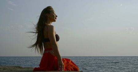 sexy woman is sitting on concrete embankment on seacoast in daytime, enjoying ocean breeze Standard-Bild - 129362690