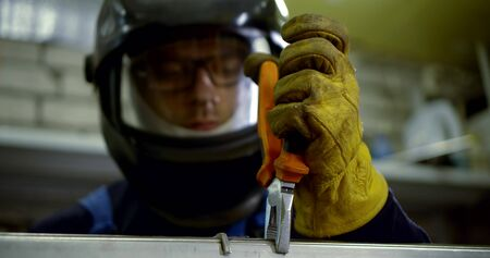 welder connects metal parts to machine with pliers in shop Stock Photo