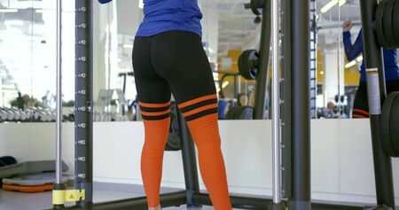 slim lady does squatting with barbell at mirror in gym