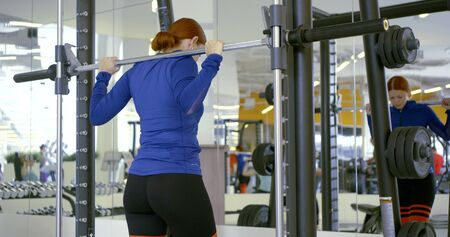 sportswoman has training with barbell at mirror slow motion
