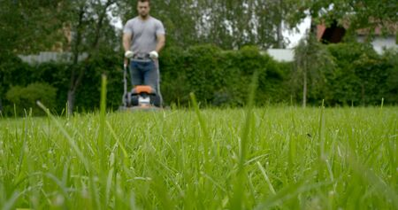 young man in t-shirt and working gloves uses modern lawn mower to cut green grass in garden low angle shot slow motion Stock fotó