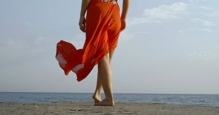 Slender girl legs on the beach in windy. weather in the afternoon in a red skirt