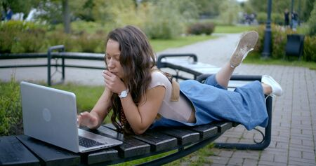 serious lady lies on bench types on laptop and closes comp Banco de Imagens