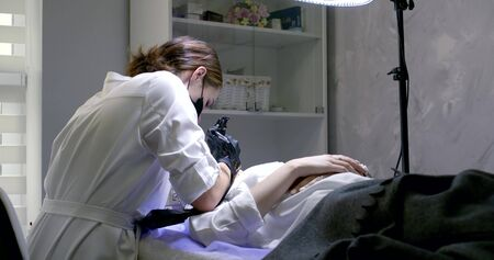 cosmetologist in coat applies permanent make-up in salon