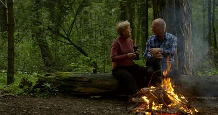 elderly hikers are resting in forest near fire, woman is offering to her husband warm tea