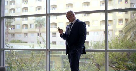 A bald businessman in a classic suit and glasses walks near the panoramic window, he is in the business center, he has a phone in his hands, he looks at it and smiles, thinks.