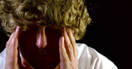 Close-up portrait of a curly-haired man on a black background. Headache from the problems of life depression