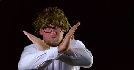 Curly-haired man with glasses on a black isolated background shows his hands and facial expressions gestures of denial and denial