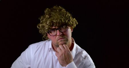 Close-up portrait of a curly-haired man with glasses on a black background in a white shirt. Dissatisfied denies head and cesta hands