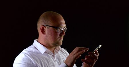 Adult bald bespectacled man holding phone and scrolling screen after typing message, isolated black background