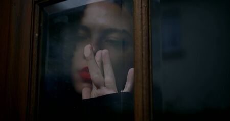 A close-up portrait of a searing brunette with curly hair, red lipstick on her face, piercings in her nose and above her lip. She is outside the window and runs her fingers thoughtfully over it.