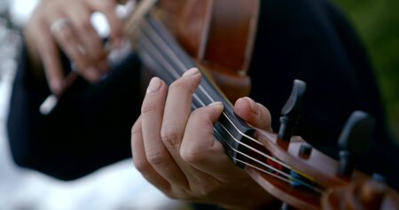 Close - up of a man playing the violin. He fingers the strings.