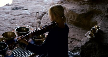 a blonde woman sits on a stone surface and conducts sound therapy, massage with sound vibrations, plays the violin, there are bowls around her.